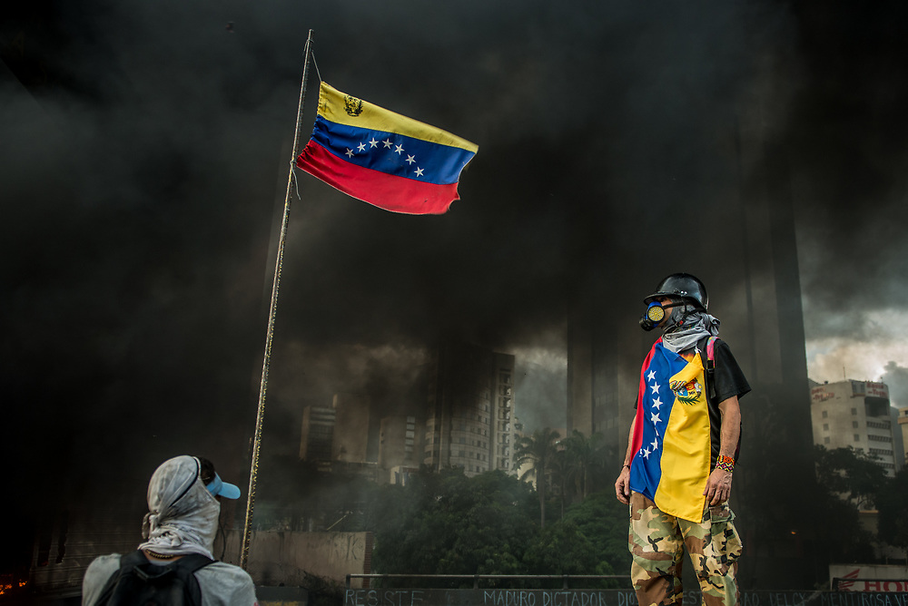 "CARACAS, VENEZUELA - MAY 27, 2017:  Anti-government protesters of ""The Resistance""  during a lull in fighting as an industrial sized truck that protesters highjacked and used as a roadblock after taking over the main highway that runs through Caracas, burns in the background.  The streets of Caracas and other cities across Venezuela have been filled with tens of thousands of demonstrators for nearly 100 days of massive protests, held since April 1st. Protesters are enraged at the government for becoming an increasingly repressive, authoritarian regime that has delayed elections, used armed government loyalist to threaten dissidents, called for the Constitution to be re-written to favor them, jailed and tortured protesters and members of the political opposition, and whose corruption and failed economic policy has caused the current economic crisis that has led to widespread food and medicine shortages across the country.  Independent local media report nearly 100 people have been killed during protests and protest-related riots and looting.  The government currently only officially reports 75 deaths.  Over 2,000 people have been injured, and over 3,000 protesters have been detained by authorities.  PHOTO: Meridith Kohut"