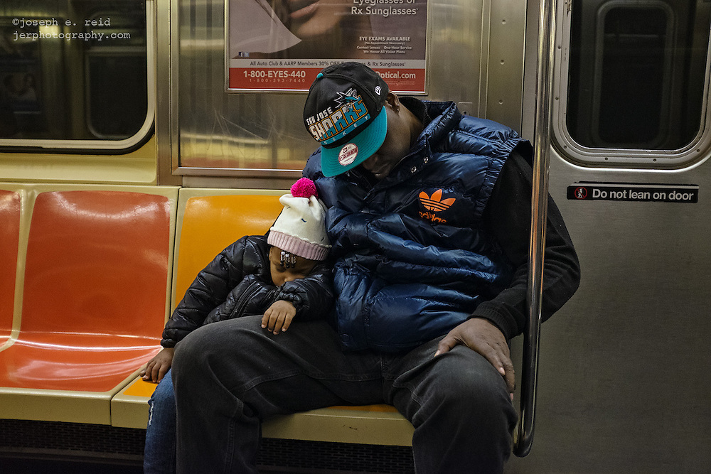 Man and child sleeping together on subway, New York, NY, US