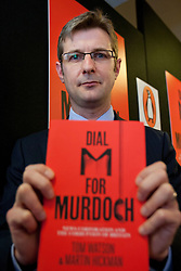 "© licensed to London News Pictures. London, UK 19/04/2012. Martin Hickman posing with his book after the press conference to launch of his book with Tom Watson on the hacking affair called ""Dial M for Murdoch"" in central London today. Photo credit: Tolga Akmen/LNP"