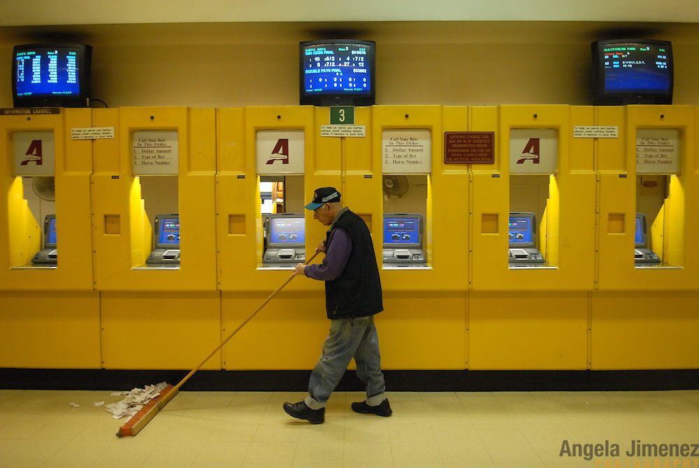 An employee sweeps up the losing tickets which litter the floor at the Aqueduct racetrack in New York City after the end of the last live race on February 16, 2007...Betting on the horses is still a popular game and the money still flows, but off track betting and other forms of entertainment have eroded live attendance at the races.  The daily diehard betters and horse lovers who sparsely populate the place on work days are joined by a bigger crowd on the weekends. ..The Aqueduct, located in Ozone Park, Queens, is the only horse racing track in New York City and probably the coldest in the country (most of the others are in Kentucky, Florida or California). Horses race on the winterized inner dirt rack from January 1st through the end of April. Aqueduct was built in 1894, renovated in 1959, then opened for winter racing in 1975. It is the winter race track operated by the New York Racing Association (NYRA), which also runs Belmont and Saratoga in the warm seasons. Betters at Aqueduct watch and bet on the nine daily live races and all other races around the country via Simulcast. ..