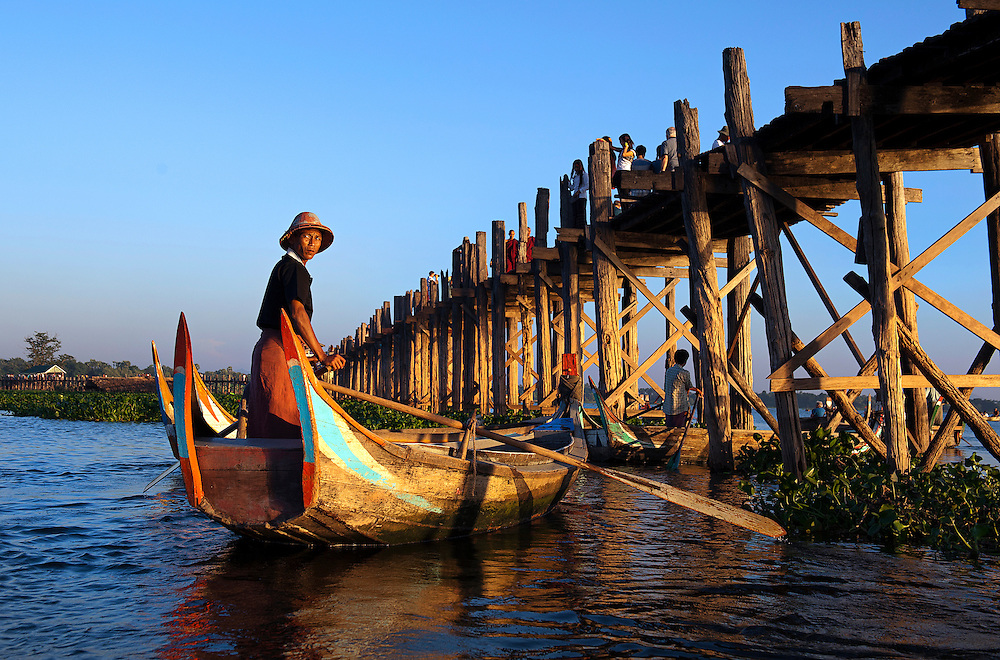 A boatman rowing at sunset under the bridge at U-Bien, Myanmar