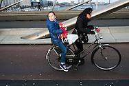 Nederland,  Rotterdam, 2 febr 2014<br /> Erasmusbrug met fietser van oosterse afkomst met dochter achterop de fiets <br /> Foto: Michiel Wijnbergh