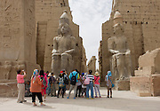 Tourist groups stand and photograph beneath the giant colossi at the entrance of the ancient Egyptian Luxor Temple, Nile Valley, Egypt. The temple was built by Amenhotep III, completed by Tutankhamun then added to by Rameses II. Towards the rear is a granite shrine dedicated to Alexander the Great and in another part, was a Roman encampment. The temple has been in almost continuous use as a place of worship right up to the present day.
