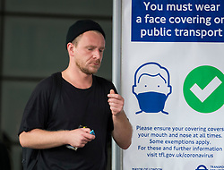 © Licensed to London News Pictures. 24/07/2020. London, UK. A commuter not wearing a face mask while leaving Tottenham Court Road station in central London, on the day that the wearing of mask in stations becomes compulsory. The UK Government has published formal guidance on spaces where the wearing of masks will now be mandatory, including in shops, supermarkets and shopping centres. Photo credit: Ben Cawthra/LNP