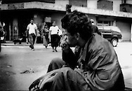 Guatemalan man sits on curb of busy Guatemala City street sniffing glue or solvent. Inhaling solvents has become a chronic problem in poverty stricken Central America.  Many young migrants head north to the United States in an attempt to rid themselves of the habit and get off the streets.