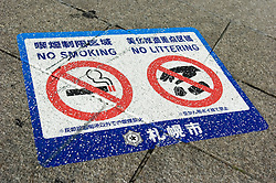 Sign on pavement in Sapporo warning of smoking and littering ban in Japan