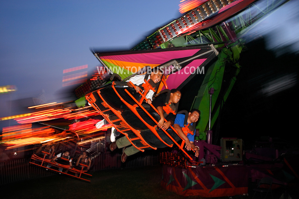 Mechanicstown, N.Y. - People enjoy a hang glider ride at dusk at the Orange County Fair on July 29, 2006. ©Tom Bushey