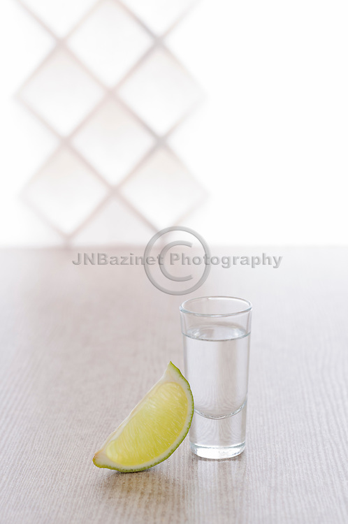 Tequila shot with wedge of lime against clean, bright background.