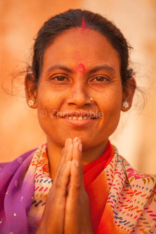 A Hindu woman greets a stranger with the traditional Hindu greeting of Namaste in Varanasi India.