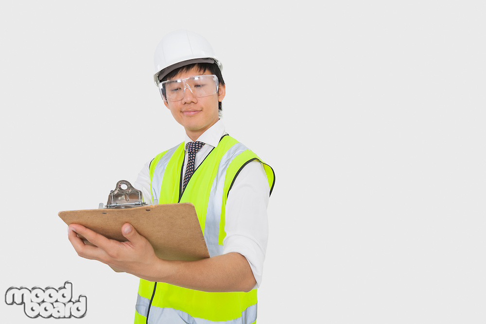 Confident construction worker holding clipboard in office