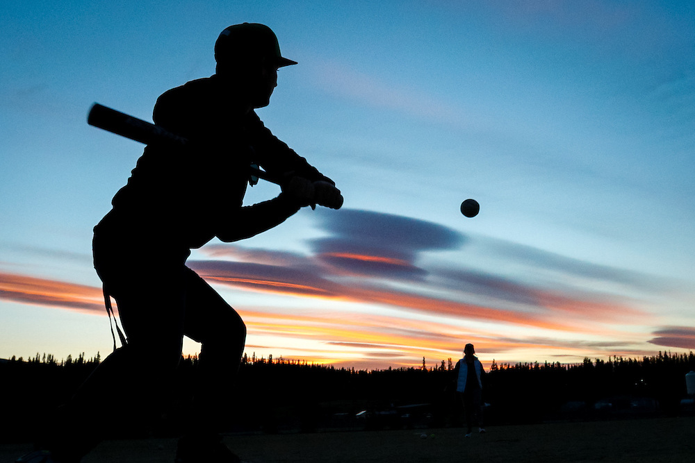 Aiden Allen keeps his eye on the ball during a sunset softball session in Whitehorse.