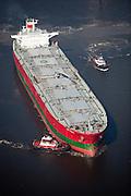 Tug churning up the bottom of the Houston Ship Channel pushing a Supertanker leaving Oiltanking Houston, Inc. tank farm.