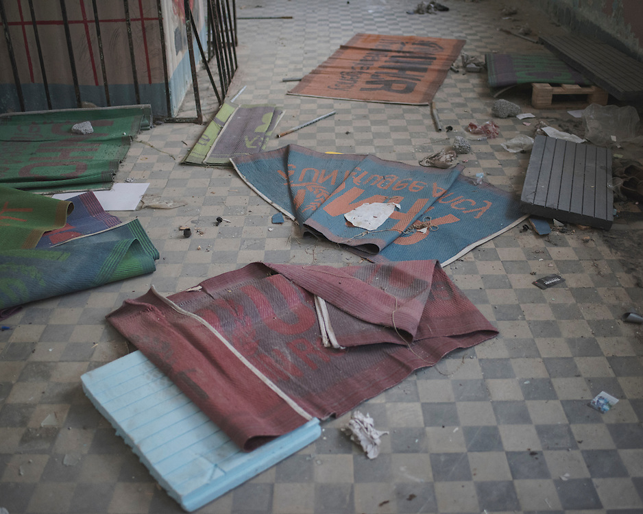 Discarded UNHCR prayer mats in an abandoned building at a now-closed refugee camp at the port of Lakki.<br /> <br /> The camp was opened by volunteers in the summer of 2015 and later that year UNHCR and MSF expanded it and provided additional tents, toilets and other facilities. The camp was closed soon after the opening of a 'Hotspot' (EU-run migrant's reception centres) camp in Lepida in February 2016.