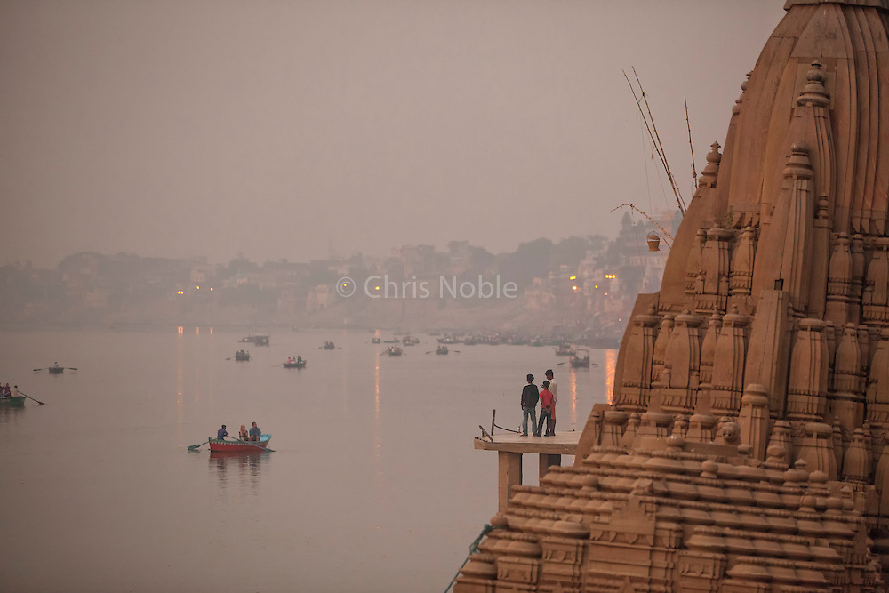 At dawn, three boys watch boats on the Ganges River near the ruins of the Shiva Temple at Scindia Ghat, Varanasi India.