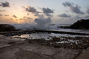 The ancient port of Caesarea, Israel at Sunset. Waves are breaking on the breakwater