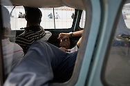 ITALY. Lampedusa:A tunisian migrant sleeps in a car in the port of Lampedusa on  March  28, 2011. Copyright Christian Minelli.