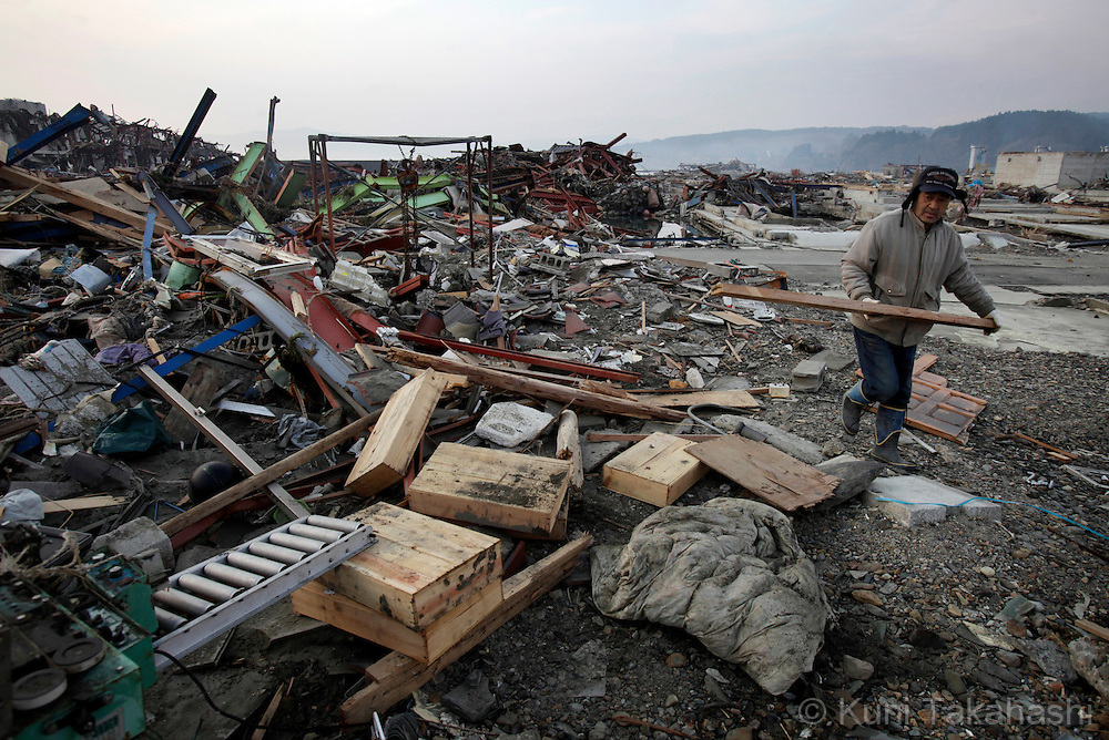 A man picks up belongings of his factory in MInamisanriku, Miyagi, Japan on March 31, 2011 after massive earthquake and tsunami hit northern Japan. More than 20,000 were killed by the disaster on March 11.<br /> Photo by Kuni Takahashi