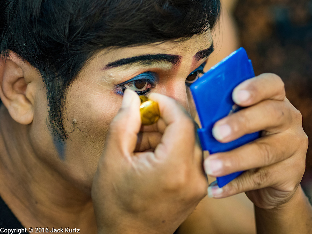 """30 JANUARY 2016 - NONTHABURI, NONTHABURI, THAILAND: A performer puts on his eye makeup before a """"likay"""" show at Wat Bua Khwan in Nonthaburi, north of Bangkok. Likay is a form of popular folk theatre that includes exposition, singing and dancing in Thailand. It uses a combination of extravagant costumes and minimally equipped stages. Intentionally vague storylines means performances rely on actors' skills of improvisation. Like better the known Chinese Opera, which it resembles, Likay is performed mostly at temple fairs and privately sponsored events, especially in rural areas. Likay operas are televised and there is a market for bootleg likay videos and live performance of likay is becoming more rare.     PHOTO BY JACK KURTZ"""