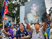 03 SEPTEMBER 2016 - BANGKOK, THAILAND:  A Pom Mahakan resident holds up a portrait of Bhumibol Adulyadej, the King of Thailand, at one of the blockaded entrances to the Pom Mahakan community. Hundreds of people from the Pom Mahakan community and other communities in Bangkok barricaded themselves in the Pom Mahakan Fort to prevent Bangkok officials from tearing down the homes in the community Saturday. The city had issued eviction notices and said they would reclaim the land in the historic fort from the community. People prevented the city workers from getting into the fort. After negotiations with community leaders, Bangkok officials were allowed to tear down 12 homes that had either been abandoned or whose owners had agreed to move. The remaining 44 families who live in the fort have vowed to stay.     PHOTO BY JACK KURTZ