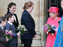 The Queen is presented with flowers from schoolchildren as she leaves the annual Commonwealth Observance at Westminster Abbey in London, Monday, 10th March 2014. Picture by Stephen Lock / i-Images