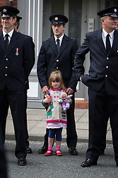 © Licensed to London News Pictures . 02/09/2013 . Bury , UK . A young girl amongst 100s of fire service personnel lining the streets of Bury leading up to the church . The funeral of fireman Stephen Hunt at Bury Parish Church today (Tuesday 3rd September 2013) . Stephen Hunt died whilst tackling a blaze at Paul's Hair World in Manchester City Centre in July 2013 . Photo credit : Joel Goodman/LNP