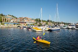 United States, Washington, Kirkland (near Seattle), woman kayaking in marina