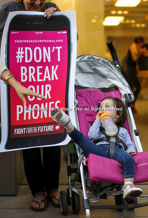 2月23日,示威者在洛杉矶一家苹果专卖店外示威。当天,示威活动在美国、甚至美国以外超过30多个城市的多家苹果零售店展开,声援苹果公司拒绝帮助美国执法部门解除一部在去年12月2日美国加州南部圣贝纳迪诺恐怖袭击案中枪手的智能手机开机密码。新华社发 (赵汉荣摄)<br /> A baby girl joins other demonstrators protest outside the Apple store, Tuesday, Feb. 23, 2016, in Los Angeles, the United States. Protesters assembled in more than 30 cities around the world to lash out at the FBI for obtaining a court order that requires Apple to make it easier to unlock an encrypted iPhone used by a gunman in December's mass murders in California. (Xinhua/Zhao Hanrong)(Photo by Ringo Chiu/PHOTOFORMULA.com)<br /> <br /> Usage Notes: This content is intended for editorial use only. For other uses, additional clearances may be required.