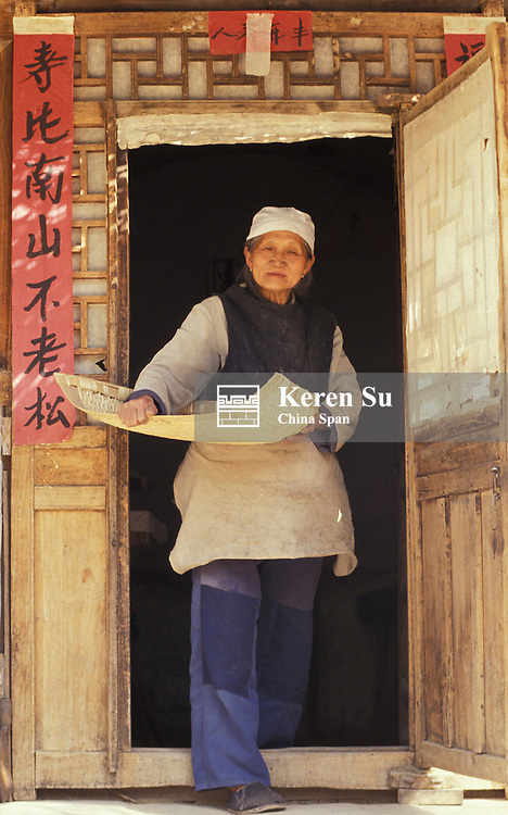 Hui woman by the doorway decorated with red poster of calligraphy couplet, Shaanxi Province, China