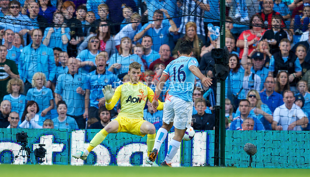 MANCHESTER, ENGLAND - Sunday, September 22, 2013: Manchester City's Sergio Aguero scores the third goal against Manchester United's goalkeeper David de Gea during the Premiership match at the City of Manchester Stadium. (Pic by David Rawcliffe/Propaganda)
