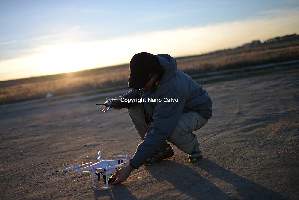 Young man flying Phantom Drone outdoors at sunset