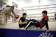 Le coach du Bhiwani Boxing Club Ms. Singh sort du ring à fin journée; deux jeunes filles viennent de terminer une session supplémentaire d'exercises abdominaux