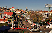 Mexican shoppers in Nogales, Sonora, Mexico, patronize businesses once popular with American tourists near the border wall that divides the area from Nogales, Arizona, USA.