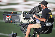 An ESPN television cameraman sits on an elevated platform while recording the events as they unfold before the Green Bay Packers 2016 NFL Pro Football Hall of Fame preseason football game against the Indianapolis Colts on Sunday, Aug. 7, 2016 in Canton, Ohio. The game was canceled for player safety reasons due to the condition of the paint on the turf field. (©Paul Anthony Spinelli)