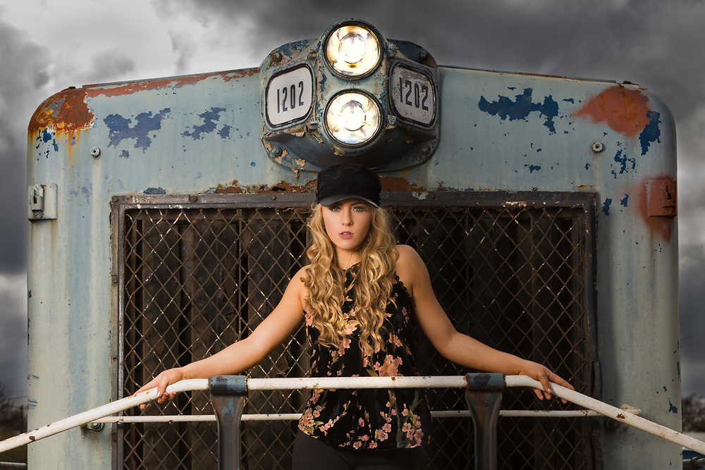 Model Brenna Smith poses on an abandoned train with storm clouds lomming behind. From a shoot with Gerard Harrison Image Theory Photoworks.