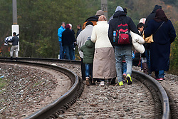 Licensed to London News Pictures. 22/10/2015. Sentilj, Slovenia. Migrants are walking on the railway tracks to train station in Spielfeld, Austria at a border crossing between Austria and Slovenia. Photo: Marko Vanovsek/LNP