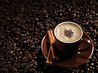 Cup of coffe latte with chocolate and cinnamon on coffee beans background