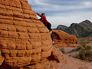 Mati Reed (age 11) climbs the Beehive sandstone formations at Valley of Fire State Park, Moapa, NV.  Less than an hour, northwest of Las Vegas this secluded valley contains dramatic red sandstone formations. ..PHOTO COPYRIGHT 2006 LANCE CHEUNG<br />