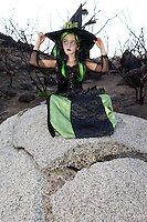 Little young girl costumed as witch sitting on rock looking away