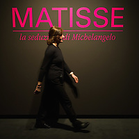 """BRESCIA, ITALY - FEBRUARY 11: A member of staff walks in front of the sign at the entrance of Matisse Exhibition at Santa Giulia Museum on February 11, 2011 in Brescia, Italy. The exhibition """"Matisse La Seduzione di Michelangelo"""" shows  180 works of the French artist and will stay open until June 12th 2011"""