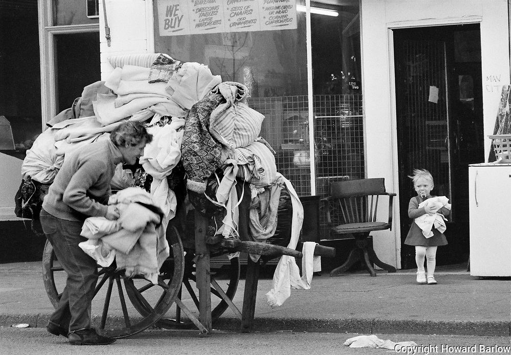 Rag and Bone man &ndash; Ardwick 1980 <br /> Playing hide and seek this little girl was helping bring out rags for the cart.<br /> I think it was opposite the Apollo theatre.<br /> The tatter was Dennis Holloran who worked for Bessie McKail's rag yard in Salford. She started the business in the 1930's through to 1980's.