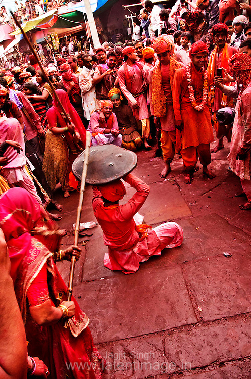 Man from Nandgaon village who are led away by the women folks from Barsana are being with the sticks during Lathmar Holi. Braj ki Holi