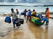 18 JULY 2016 - KUTA, BALI, INDONESIA:  Fishermen land their small outrigger canoe at Pasar Ikan pantai Kedonganan, a fishing pier and market in Kuta, Bali.   PHOTO BY JACK KURTZ