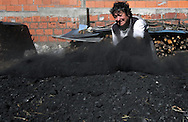 Maria Emilia Martins uses a spade to cover with sand the pile of wood to make the sharcoal stove . In the village of Pilado in the county of Marinha Grande, sharcoal production goes back to the sixth century, always executed by women, today due to unemployment, men are taking the responsability for this handicraft industry. Sharcoal is used as an alternative  power, most of all to grill.Paulo Cunha/4see