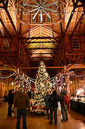 Old Bethpage, New York, USA. Decemer 26, 2014. A large traditional 1866 decorated Christmas Tree tree is under the high ceiling of the Barn wood peg spire at night, on the historic, rustic grounds of Old Bethpage Village Restoration, transformed by candlelight and Christmas decorations into a Nineteenth Century holiday experience for Long Island visitors. Candlelight Evenings are held until December 30th.