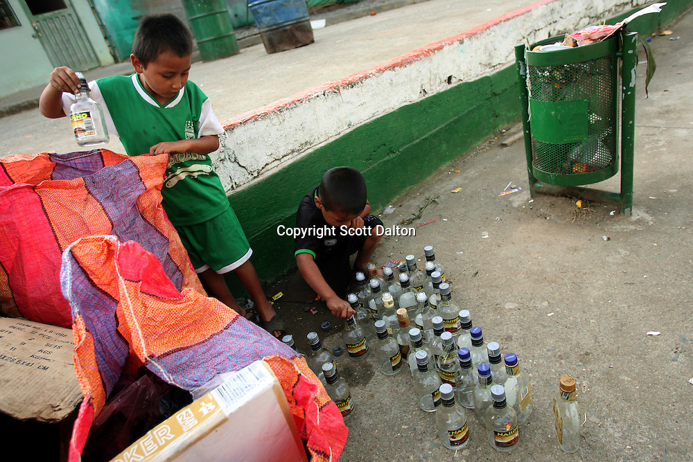 Two young boys collect the empty bottles left after a party in the town plaza in Leiva, a small remote village in the southern Colombian state of Nariño, on Monday, June 25, 2007. The boys will sell the bottles for a little extra change. (Photo/Scott Dalton)