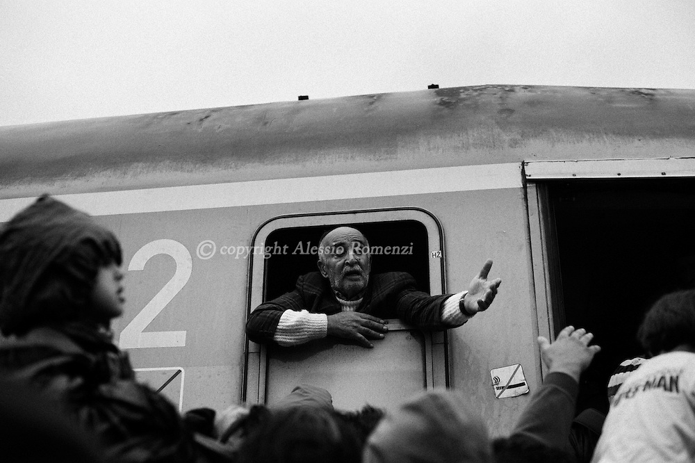 Croatia: A man puts her arms out for his relative as migrants desperately try and board a train heading for Zagreb from Tovarnik station. Alessio Romenzi