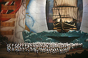 Members of the Royal Marines band march under a giant backdrop of Nelson's flagship HMS Victory during the Royal Tournament.