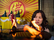 27 JANUARY 2017 - BANGKOK, THAILAND: A woman lights prayer candles at Wat Mangkon Kamalawat on Chinese New Year in Bangkok. 2017 is the Year of the Rooster in the Chinese zodiac. This year's Lunar New Year festivities in Bangkok were toned down because many people are still mourning the death Bhumibol Adulyadej, the Late King of Thailand, who died on Oct 13, 2016. Chinese New Year is widely celebrated in Thailand, because ethnic Chinese are about 15% of the Thai population.       PHOTO BY JACK KURTZ