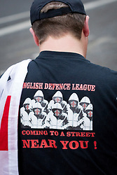 """© Licensed to London News Pictures . 12/10/2013 . Bradford , UK . An EDL supporter wearing a t shirt reading """" English Defence League coming to s a street near you """" . The EDL hold a demonstration in Bradford today (Saturday 12th October 2013) . It is their first demonstration since leaders Stephen Yaxley-Lennon (aka Tommy Robinson ) and Kevin Carroll quit . Approximately 500 protesters gathered near the city centre . Photo credit : Joel Goodman/LNP"""
