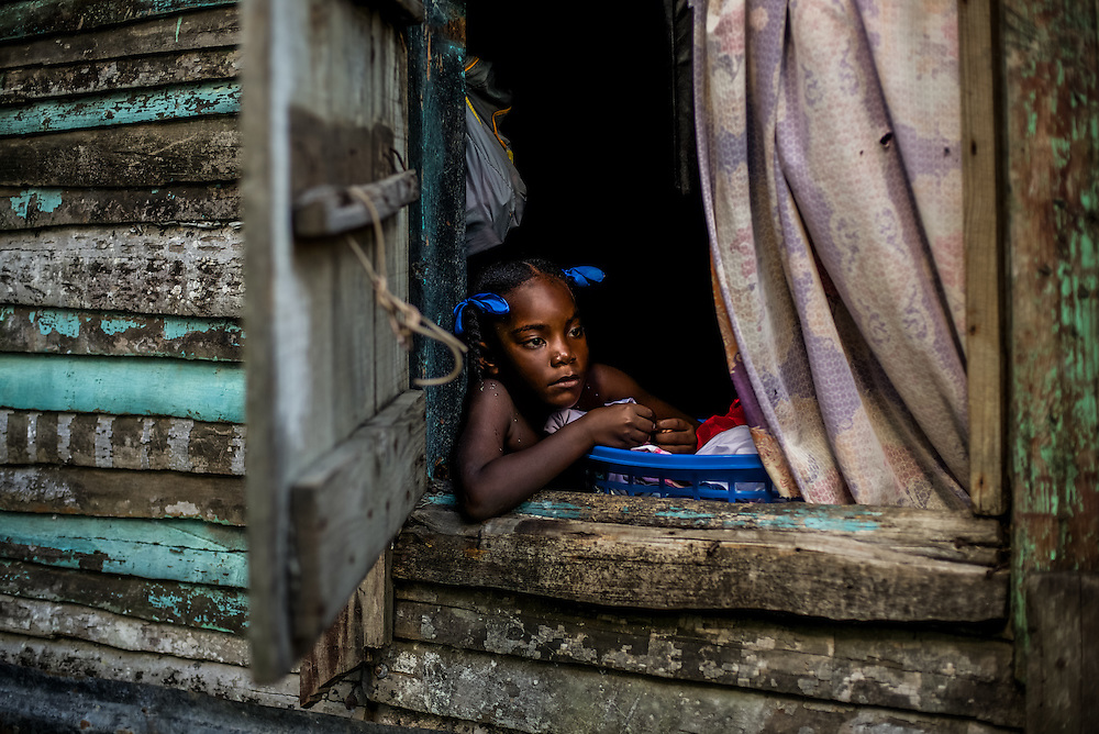 EL SEIBO, DOMINICAN REPUBLIC - OCTOBER 12, 2013: Digna Javier Batista looks out of the window in an impoverished batey on a sugarcane plantation in El Seibo.  Batista was born in the Dominican Republic to Haitian parents, and is therefore affected by  judgment TC/0168, handed down by the Constitutional Court of the Dominican Republic.  The ruling essentially revokes Dominican citizenship from tens of thousands of people born in the Dominican Republic, which means they cannot have access to government services, id's necessary to travel and work, and the children cannot attend public school. The Inter-American Commission on Human Rights has expressed that the ruling would leave affected people stateless, which is a violation of the American Convention on Human Rights.